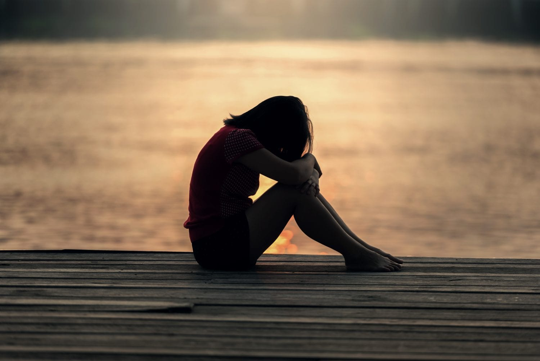 Sad person on lake dock