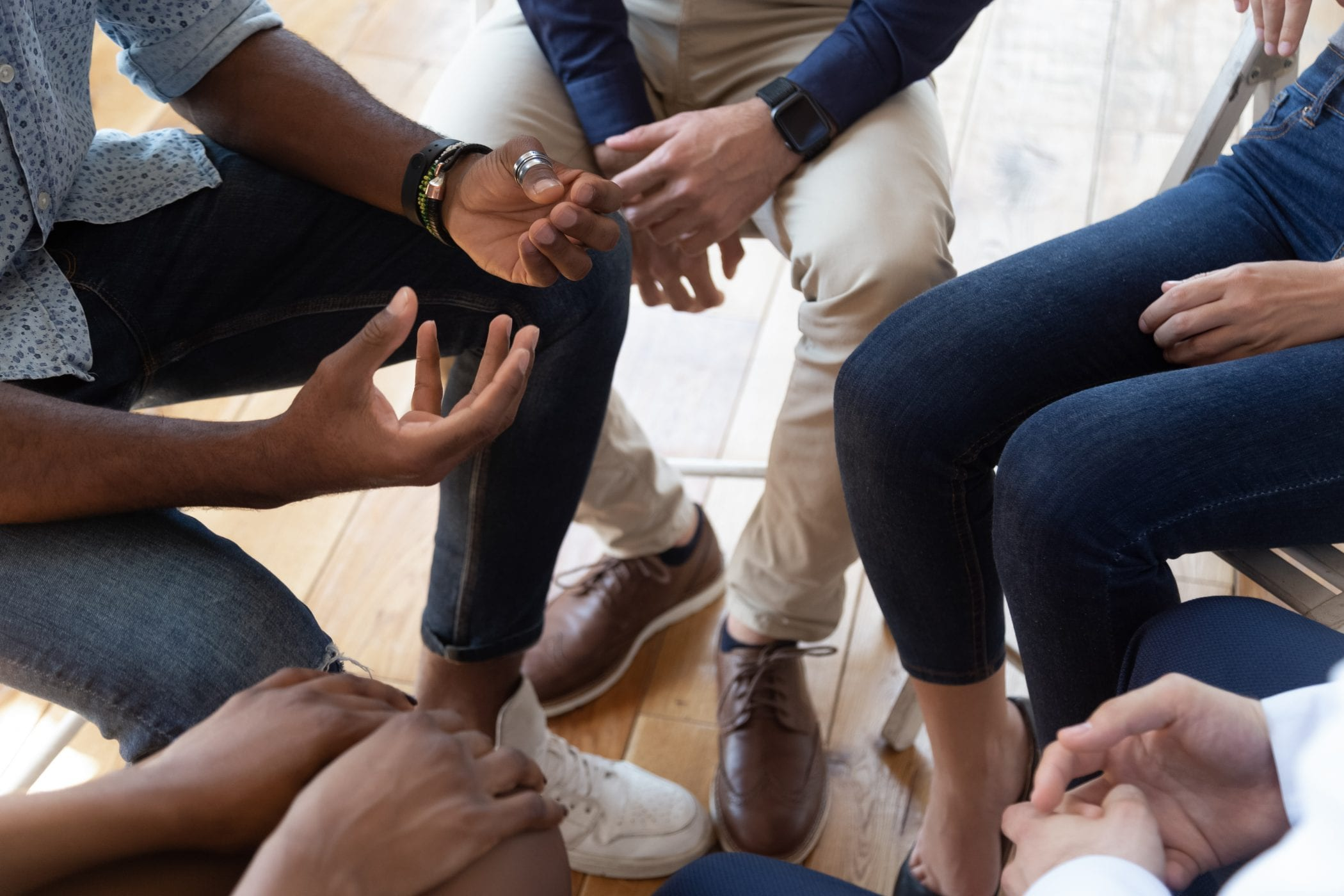 People sitting in circle share problems during psychological rehab session