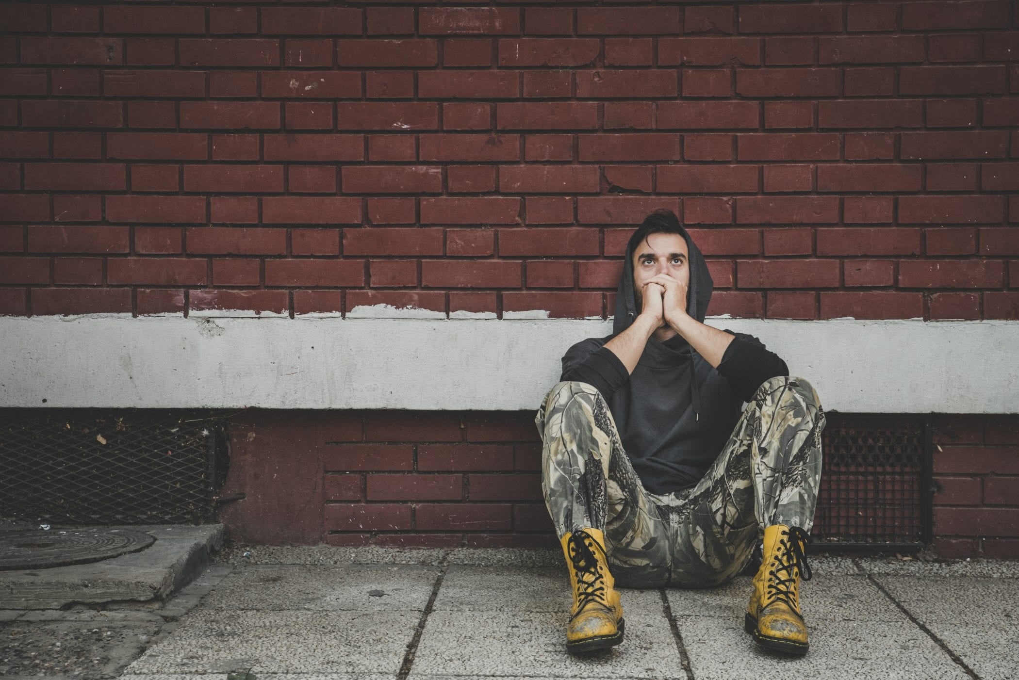 Homeless, Homeless man drug and alcohol addict sitting alone and depressed on the street leaning against a red brick building wall feeling anxious and lonely, social documentary concept